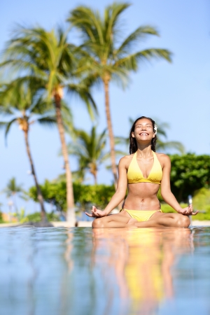 retreat: Serene meditating woman relaxing at luxury travel holiday vacation resort Stock Photo