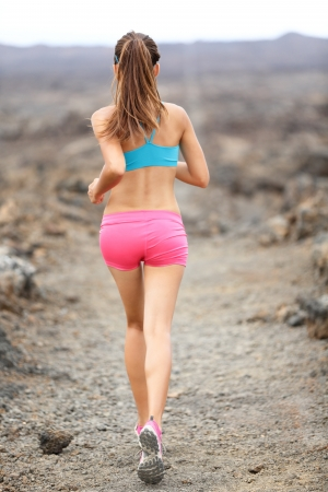 Rear view showing back from behind of woman runner on Hawaii. photo