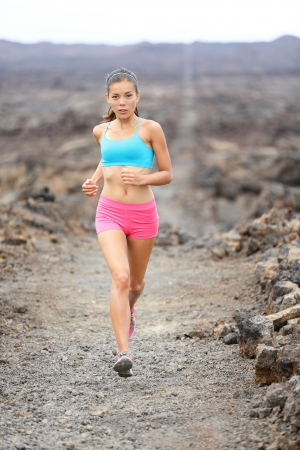 Female athlete jogging training for marathon run outside in beautiful landscape photo