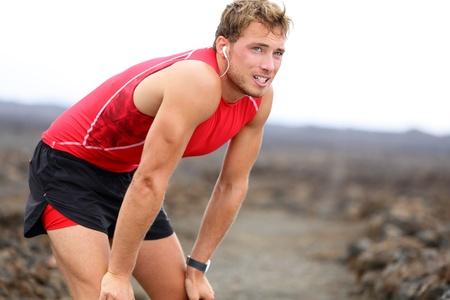 sudoroso: Hombre modelo de fitness y triatleta relajarse mirando con auriculares escuchando m�sica