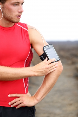 runner man listening to music adjusting settings on armband for smartphone photo