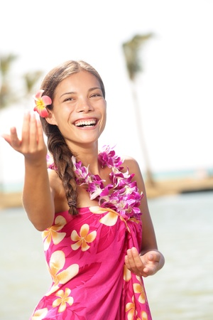 Hula dancer woman dancing hula dance on Hawaii wearing Hawaiian orchid flower lei smiling happy on beach photo