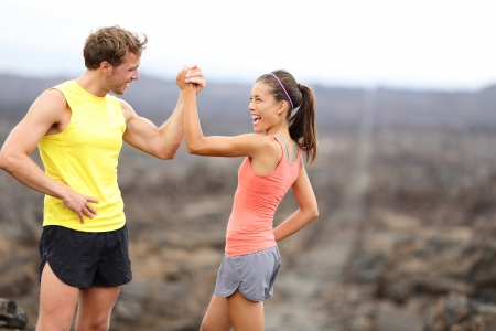 Fitness sport running couple celebrating cheerful and happy giving high five energetic and cheering