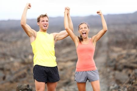 personas celebrando: Que anima la celebraci�n feliz fitness corredor pareja con los brazos levantados en ganar expresi�n gesto al aire libre Foto de archivo