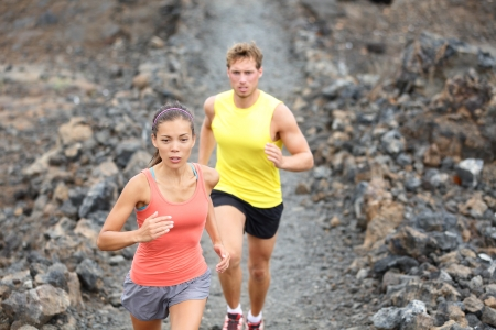 Runners couple running on trail in cross country run outdoors training photo