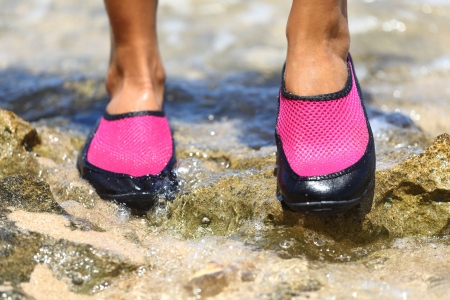 Closeup detail of the feet of a woman wearing bright pink neoprene water shoes standing on rocks photo