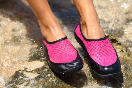 Closeup detail of the feet of a woman wearing bright pink neoprene water shoes standing on rocks Stock Photo - 19983207