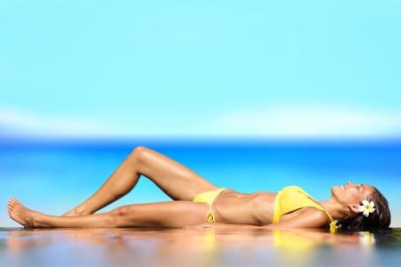 niñas en bikini: La mujer acostada de espaldas en la arena mojada frente al océano en la playa tomando el sol en bikini
