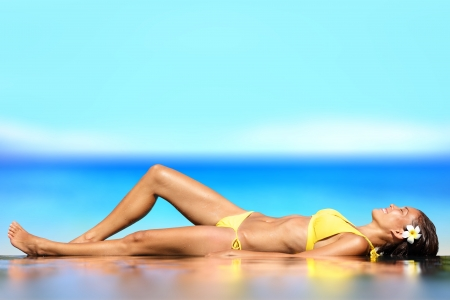 young girl bikini: Woman lying on her back on wet sand in front of the ocean at the seaside sunbathing in her bikini Stock Photo