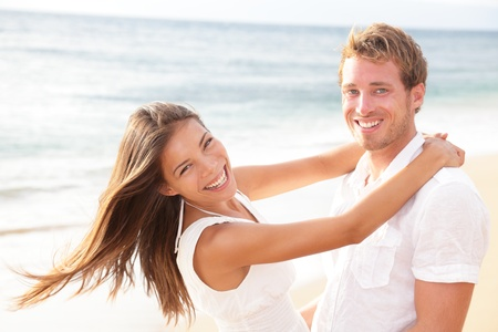 ビーチで楽しく愛幸せなカップルを抱いて、お互いの周りを保持