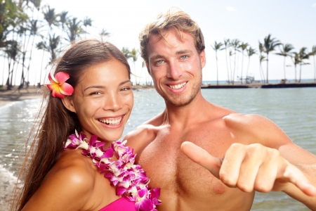 lei: Woman wearing flower lei garland and man giving shaka aloha hand sign on vacation travel Stock Photo