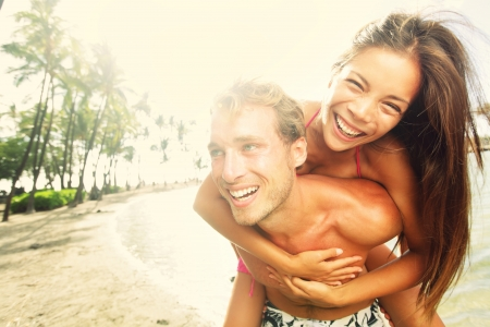 Happy young joyful couple having beach fun piggybacking laughing together during summer holidays vacation on tropical beach photo