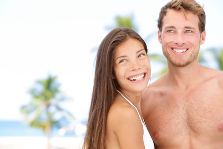 looking sideways: Romantic young couple on beach vacation smiling happy