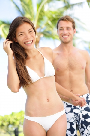 Joyful multi-ethnic young couple laughing elated together on tropical beach holiday photo