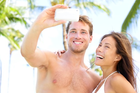 Vacation couple on beach taking pictures with camera phone photo