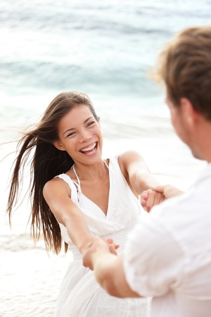 Beach summer vacation fun with playful young couple playing together enjoying their date or honeymoon photo