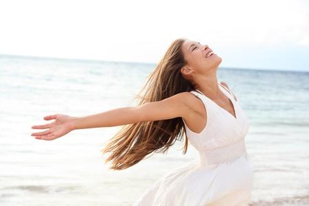 libertad: Mujer que se relaja en la playa disfrutando de la libertad de verano con los brazos abiertos y el pelo en el viento junto al mar de agua Foto de archivo