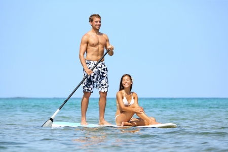 surfing: Beach fun couple on stand up paddleboard surfboard surfing together in ocean sea on Big Island, Hawaii Beautiful young multi-ethnic couple, mixed race Asian woman and Caucasian man doing water sport.