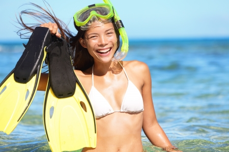 watersport: snorkeling fun on beach - woman showing fins, snorkel and mask while doing watersport on summer holidays travel vacation on Maui, Hawaii, USA. Beautiful young mixed race Asian Caucasian bikini model. Stock Photo