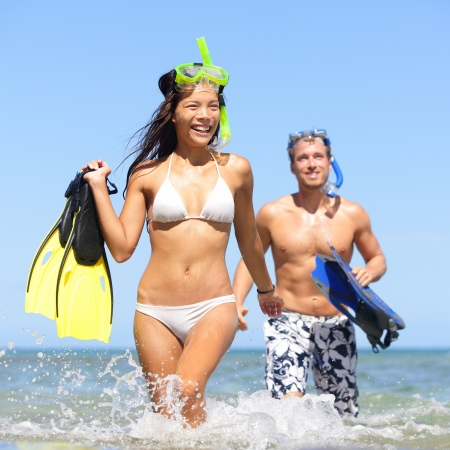 snorkelling: Beach couple having fun on vacation travel with snorkel, mask and fins. Happy interracial multi-ethnic young couple running excited at tropical beach during summer holidays at Maui, Hawaii, USA