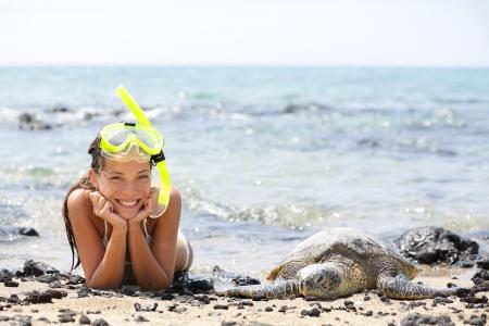 snorkle: Hawaii girl swimming snorkeling with sea turtles. Happy woman on vacation with snorkel mask lying on Hawaiian sand on Big Island next to sea turtle. Hawaii, USA travel lifestyle image.