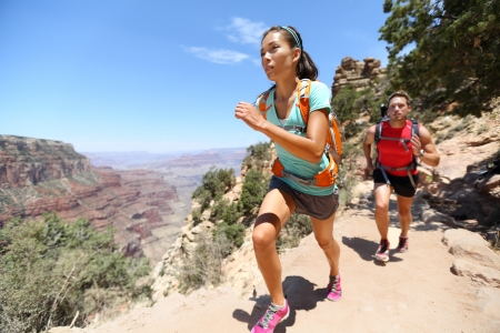 trail: Trail running cross-country runners in race on path in Grand Canyon, USA. Fit athletes jogging and training together in beautiful nature landscape. Asian fitness woman, Caucasian fit model.