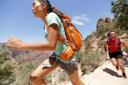 Trail runner woman in cross country running race in Grand Canyon. Couple training working out together sprinting fast at speed in beautiful landscape nature in Grand Canyon, Arizona, USA. photo