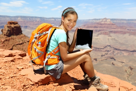 south kaibab trail: Tablet computer woman hiking in Grand Canyon showing using travel app or map during her hike. Multiracial relaxing on South Kaibab Trail, south rim of Grand Canyon, Arizona, USA. Stock Photo