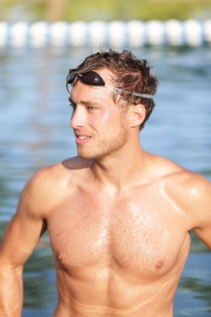 pecs: Swimming man portrait - handsome male swimmer in outdoors pool wearing swimming glasses. Good-looking young man fitness sports model relaxing after workout for triathlon. Stock Photo