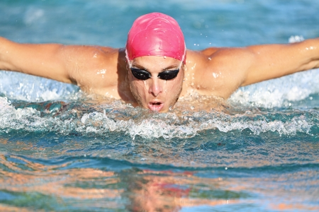 cardio fitness: Swimming man athlete butterfly swim stroke. Male sport fitness guy using swimming goggles and cap training hard in outdoor pool. Professional male sports fitness model. Stock Photo