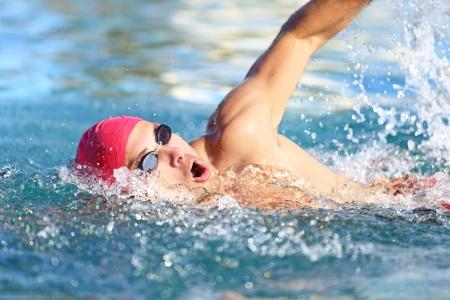 Man zwemmer zwemmen crawl in blauw water. Portret van een atletische jonge mannelijke triatleet zwemmen crawl die een roze pet en zwembril tijdje. Triatleet training voor triathlon. Stockfoto