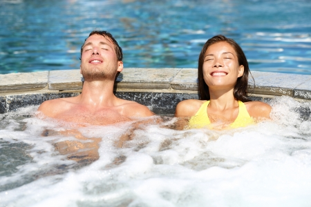 whirlpools: Spa couple relaxing enjoying hot tub bubble bath outdoors on romantic summer vacation travel holidays or honeymoon. Young interracial couple in love, Asian woman, Caucasian man.