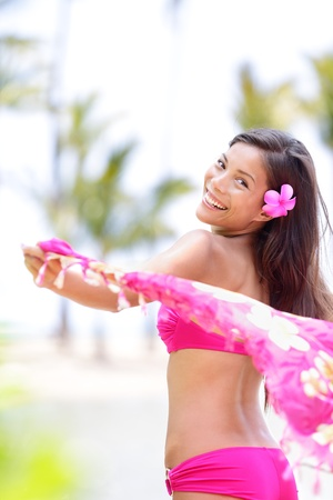 Natural beauty ethnic woman happy on beach waving pink scarf in joy