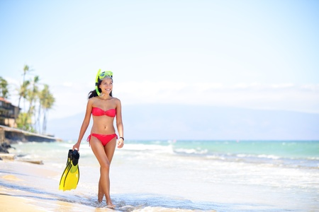 Girl in bikini with snorkel coming out of water after swimming and snorkeling in beautiful blue ocean Stock Photo - 20047556