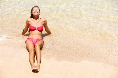 bikini girl sunbathing at beach photo