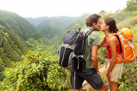 backpacking: Couple in love kissing while hiking on Hawaii. Romantic young couple hikers during hike in beautiful mountain forest nature. Healthy lifestyle multi-ethnic couple on Waihee ridge trail, Maui, USA Stock Photo