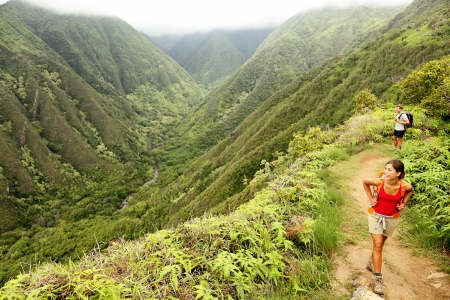 Young woman and man hikers walking in beautiful lush Hawaiian forest nature landscape in mountains