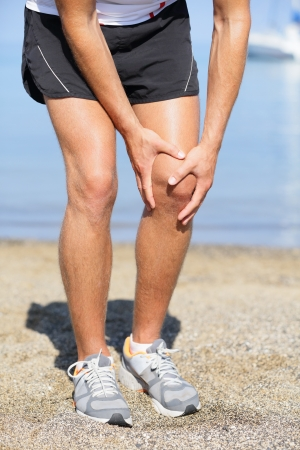 strain: Closed up view of the hands of a man out jogging on the beach clutching his knee as though in pain