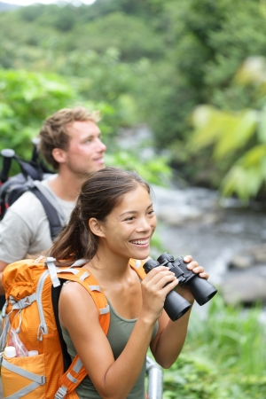 binoculars: Hiking couple of hikers in outdoor activity wearing backpacks
