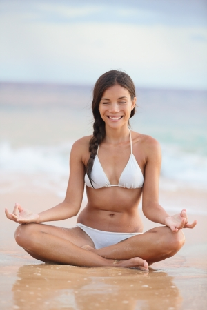 Meditation - woman on beach meditating by ocean sea smiling serene and happy. photo