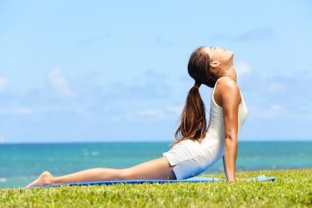 Fitness Yoga Frau, die sich abdominalen Bauchmuskulatur in cobra Körperhaltung, bhujangasana. Fit Fitness-Mädchen streckte nach Ausübung außerhalb am Strand im Sommer. Schöne Rassen weiblichen Modell. Standard-Bild - 20560249