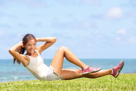 Exercising fitness woman doing sit ups outside during crossfit exercise training. Happy fit girl doing side crunches with elevated legs while smiling happy. Beautiful mixed race Asian female model.