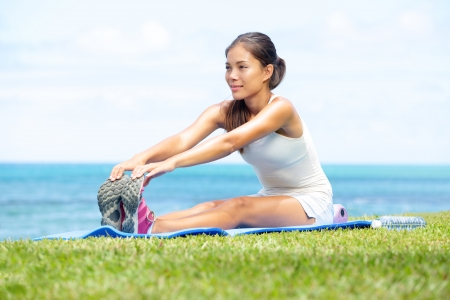 hamstring: Woman training fitness stretching legs exercise outside by the ocean sea. Beautiful fit female fitness girl model sitting on grass doing stretch exercising after workout. Mixed race Asian female model