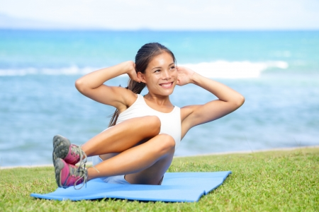 asian abs: Fitness woman exercising sit ups outside during crossfit exercise training. Happy fit girl doing side crunches with elevated legs while smiling happy. Beautiful mixed race Asian female model. Stock Photo