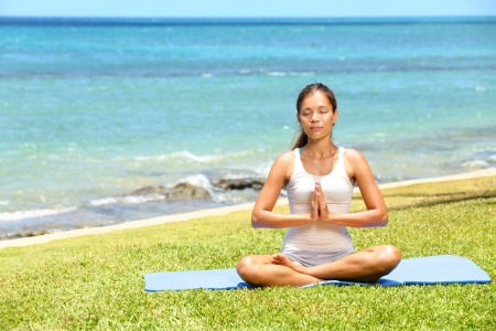 retreat: Yoga woman meditating woman relaxing by ocean sea doing the Sukhasana, easy pose. Woman in meditation in beautiful ocean landscape retreat. Meditation, yoga and relaxation concept. Stock Photo