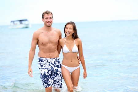 Beach couple in love walking happy in water holding hands around eachother enjoying summer holidays vacation travel. Multiracial young couple, Asian woman, Caucasian man in their 20s.