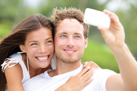 Couple fun taking self-portrait picture photos with mobile smart phone or pocket camera outdoors. Happy multiracial young couple in love taking pictures together on summer vacation. Man and woman photo