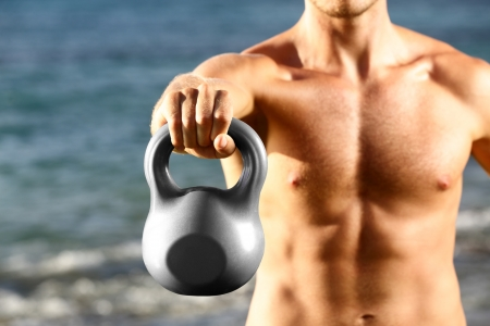 kettles: Crossfit fitness man training with kettlebells outtside. Kettlebell closeup of fit male sport athlete strength training shoulder and arms outdoors on beach. Stock Photo