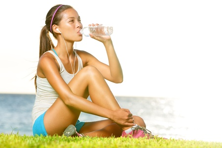 running water: Fitness woman drinking water after running training workout outside by ocean sea. Beautiful sweaty fit fitness model sitting in warm sun light enjoying water bottle listening to music in earphones. Stock Photo