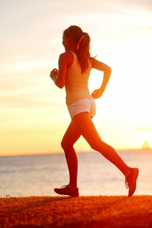 Jogging athlete woman running at sun sunset beach. Fitness runner girl training outside by the ocean sea in beautiful sunset or sunrise in full body length in summer. Stock Photo